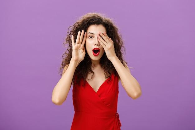 Wow niesamowite spojrzenie. zdumiona i zdziwiona ciekawska kaukaska kobieta z kręconymi włosami w czerwonej stylowej sukience otwiera usta ze zdumienia i radości zerkając jednym okiem, jednocześnie zamykając wzrok dłońmi.