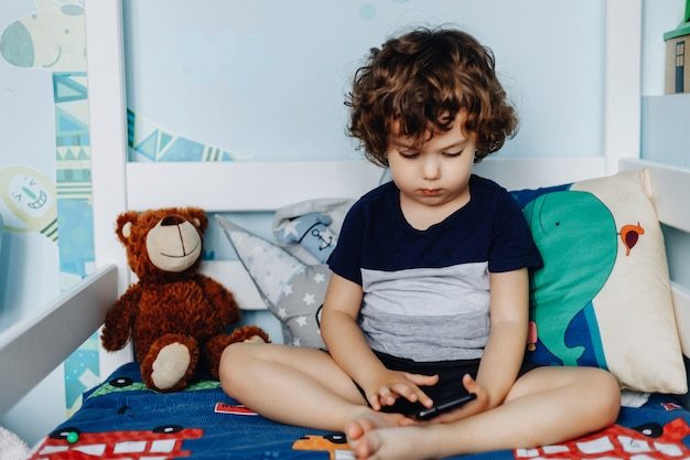 Wow, podoba mi się ten telefon. dziecko ze smartfonem. chłopiec siedzi w łóżku i gra z telefonu komórkowego. dzwonię do mojej mamy. śliczne małe dziecko trzyma telefon komórkowy w dłoniach i uważnie patrząc na ekran.