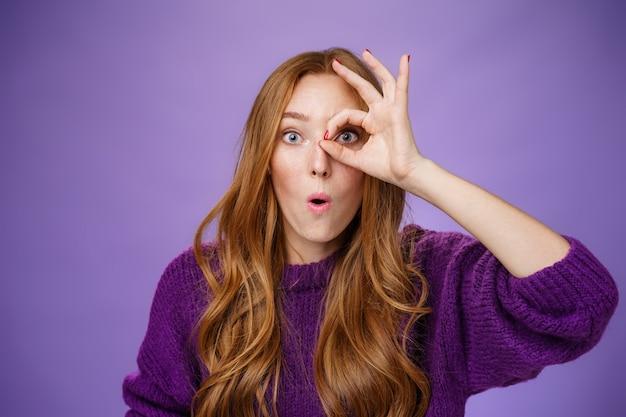 Wow super, przyjrzyj się bliżej. zaskoczona i pod wrażeniem atrakcyjna rudowłosa studentka trzymająca się w porządku lub wzdychająca koło oka nad oczami i patrząca przez, ze zdumieniem składając usta nad fioletową ścianą.