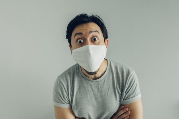 Wow twarz mężczyzny noszącego higieniczną maskę i szary t-shirt.