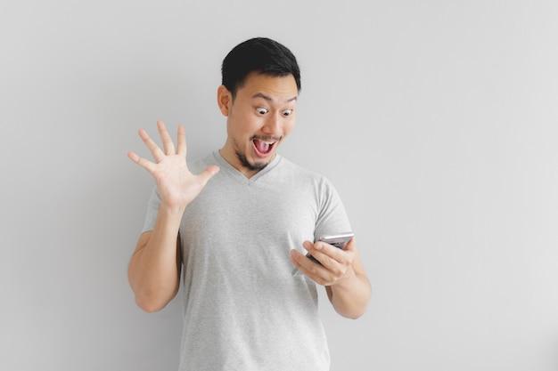 Wow twarz mężczyzny w szarej koszulce zaskoczyć na smartfonie.