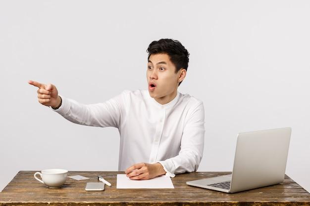 Wow, zobacz, co tam się dzieje. zaskoczony i pod wrażeniem, podekscytowany azjatycki mężczyzna, pracownik biurowy, widząc współpracownika wskazującego w lewo, z trudem łapiąc oddech, z podziwem gapiący się na przemówienia, przygotowuje dokumenty i laptopa