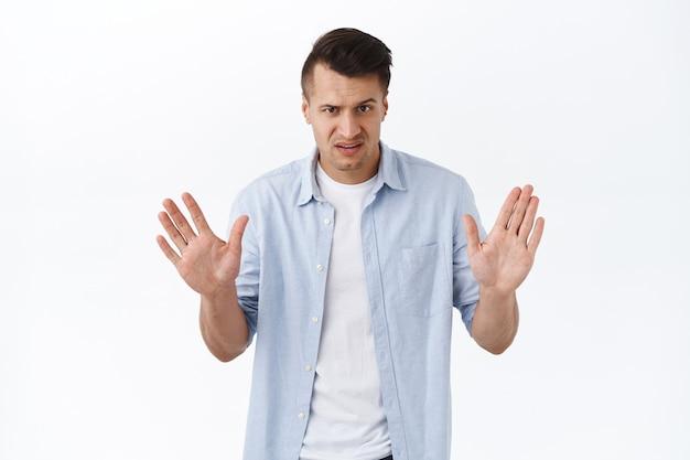Wow, zwolnij, najpierw wyjaśnij. poważnie wyglądający zdezorientowany i spokojny dorosły mężczyzna pokazujący znak stopu, próbujący zrelaksować osobę zdenerwowaną, ostrzegający, wyglądający sceptycznie i rozczarowujący, niewłaściwa rzecz