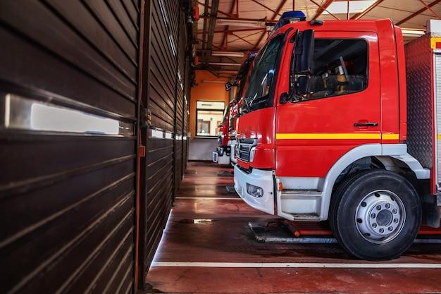 Wóz strażacki zaparkowany w straży pożarnej, przygotowany do akcji.