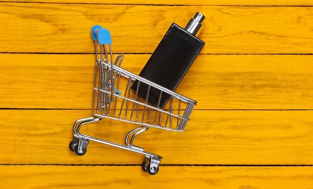 Wózek do supermarketu z butelką perfum na żółtym drewnianym