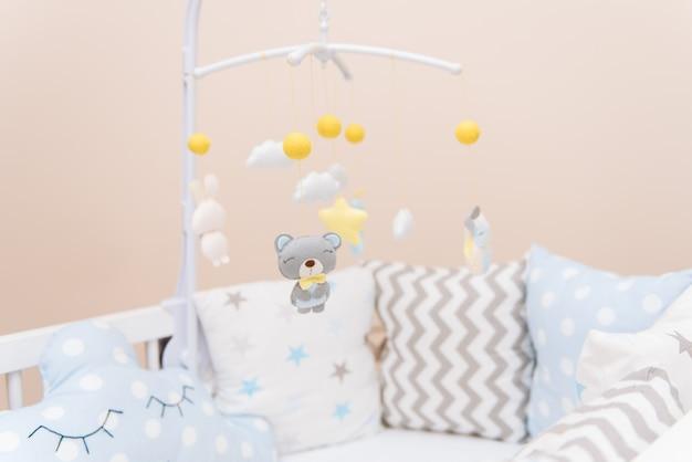 Wózek dziecięcy z różnymi zabawkami w postaci zwierząt i gwiazd, zabawki filcowe w łóżeczku