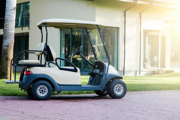Wózek golfowy jest zaparkowany w pobliżu nowoczesnego domku. samochód elektryczny na parkingu na terenie ośrodka?