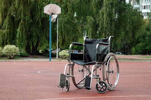 Wózek inwalidzki na boisku do koszykówki. rehabilitacja, parkinson, osoba niepełnosprawna, sparaliżowana.