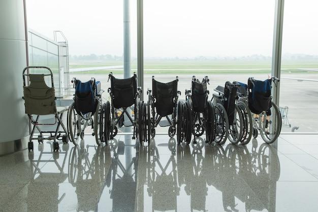 Wózek inwalidzki przy szklanym okno na lotnisku
