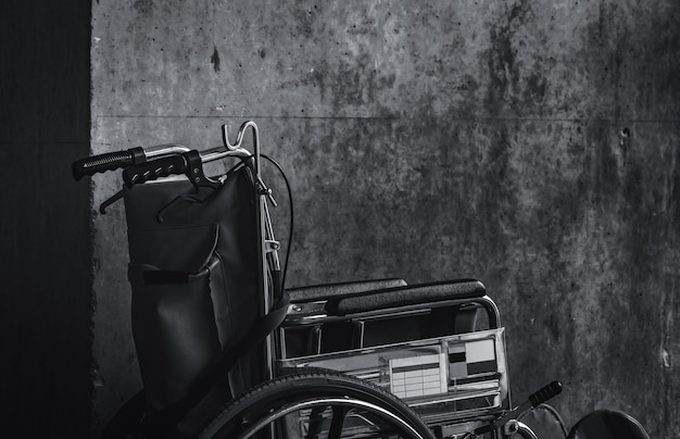 Wózek inwalidzki złożony obok ściany. smutne wieści na temat koncepcji szpitala. depresja ze starzeniem się społeczeństwa. samotny pusty wózek inwalidzki. sprzęt medyczny do obsługi pacjentów starszych i asystentów niepełnosprawnych