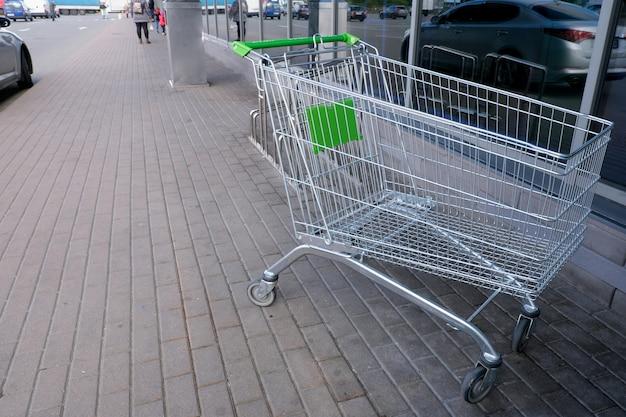 Wózek metalowy na kółkach do zakupów towarów w supermarkecie przy wejściu do sklepu, zbliżenie