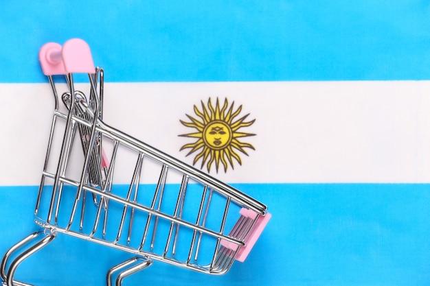Wózek mini supermarket na niewyraźne tło flaga argentyny. koncepcja zakupów.