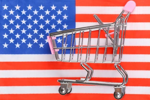 Wózek mini supermarket na niewyraźne tło flaga usa. koncepcja zakupów.