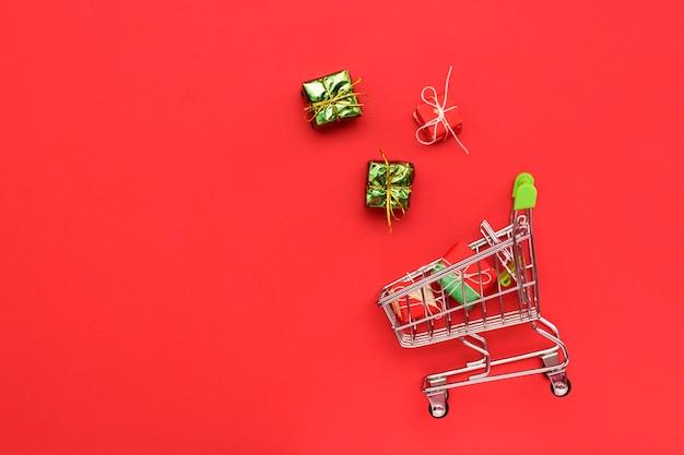 Wózek na czerwonym jasnym tle z prezentami, widok z góry.