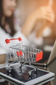 Wózek na ekranie tabletu. pomysły na zakupy online, dziewczyna używa telefonu, aby bezpośrednio kupować towary od sprzedawcy przez internet. koncepcja zakupów online