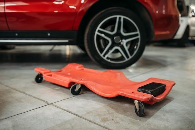 Wózek na kółkach do pracy pod spodem auta w serwisie samochodowym