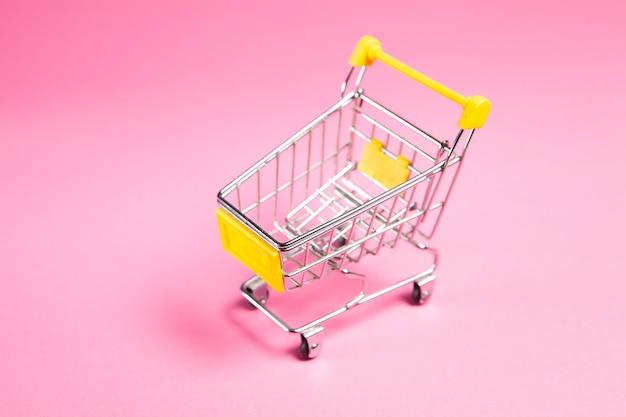 Wózek na różowym tle. koncepcja zakupów