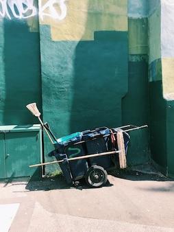 Wózek na śmieci używany do zbierania śmieci zielone tło