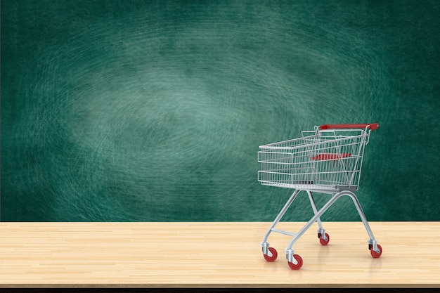 Wózek na zakupy czerwień na drewno stole z czerni deski tłem