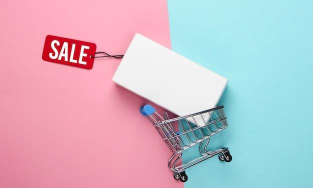 Wózek na zakupy i białe pudełko ze sprzedażą tagów na niebiesko różowym. minimalizm.