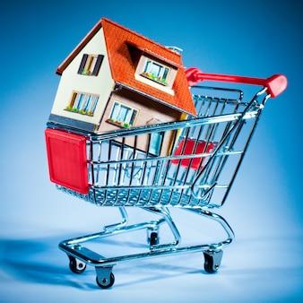 Wózek na zakupy i dom na niebieskim tle