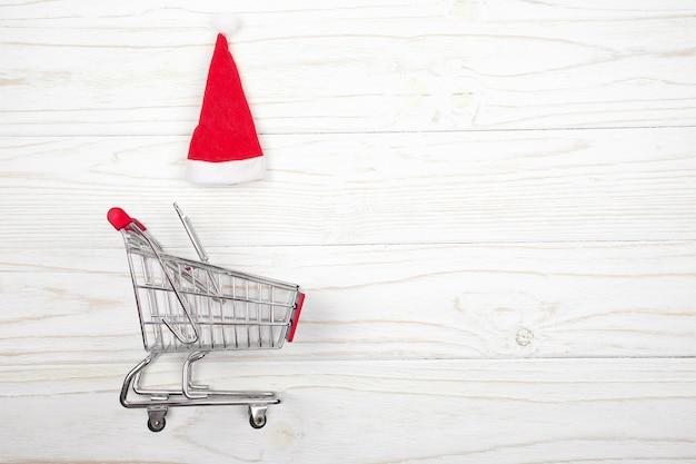 Wózek na zakupy i kapelusz świętego mikołaja na białym tle drewnianych (koncepcja sprzedaży świątecznej)
