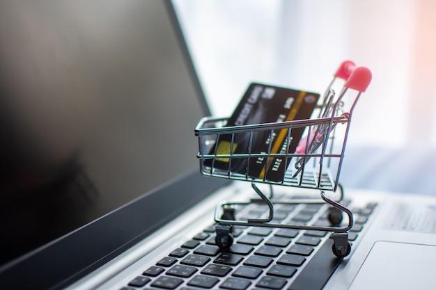 Wózek na zakupy i kredytowa karta na komputerze, robi zakupy online pojęcie.