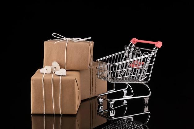 Wózek na zakupy i pudełka na prezenty. kupowanie przedstawia koncepcję, zakupy online. odosobniony