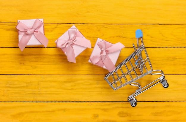 Wózek na zakupy i pudełka na prezenty z kokardkami na żółtym drewnianym