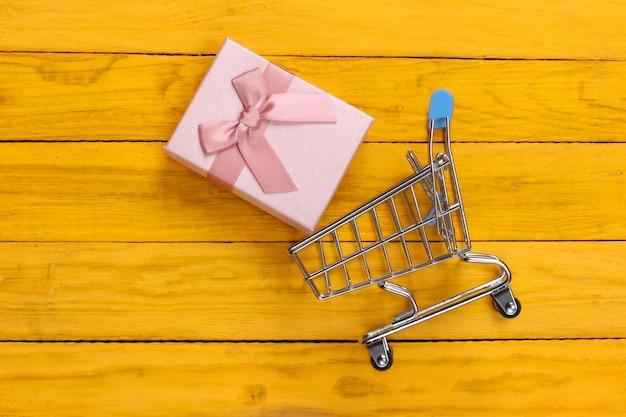 Wózek na zakupy i pudełko z kokardkami na żółtym drewnianym