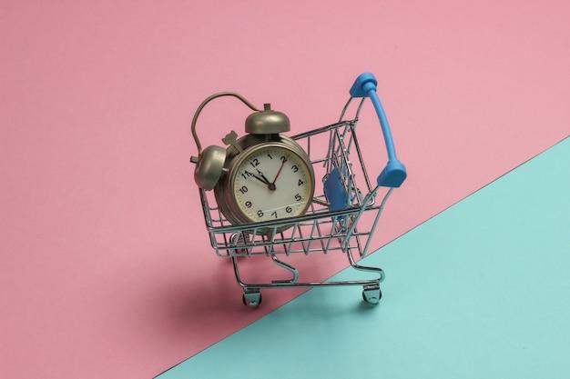 Wózek na zakupy i retro alarm na różowym niebieskim tle pastelowych. 11:55. nowy rok.
