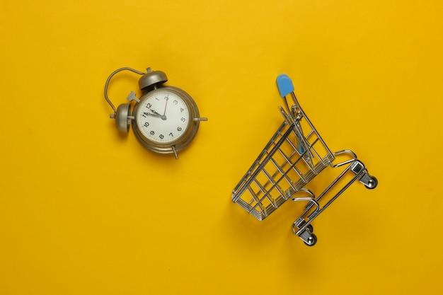 Wózek na zakupy i retro alarm na żółtym tle. 11:55. nowy rok.