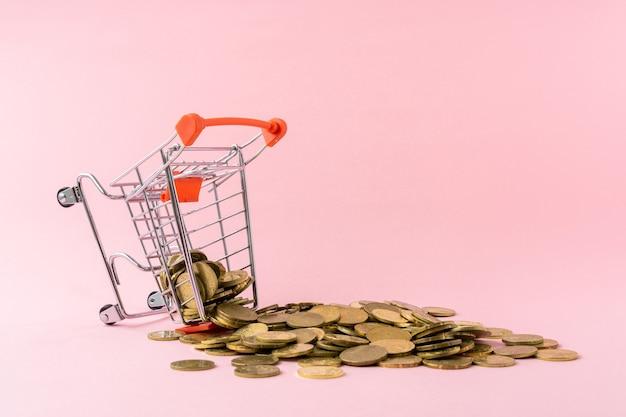 Wózek na zakupy i stos monet na różowym tle.