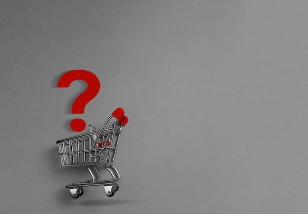Wózek na zakupy i znak zapytania na szarym tle