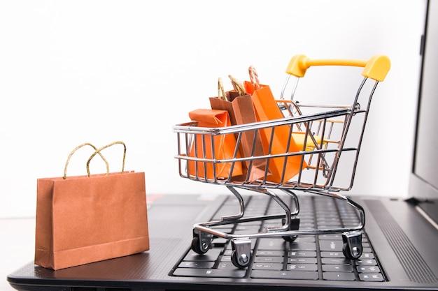 Wózek na zakupy na czarnym laptopie, białe tło, małe papierowe torby w wózku, kopia przestrzeń, koncepcja zakupów online