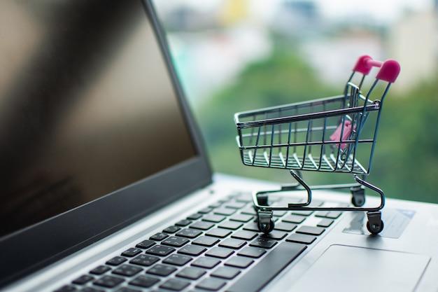 Wózek na zakupy na komputerze, robi zakupy online pojęcie.