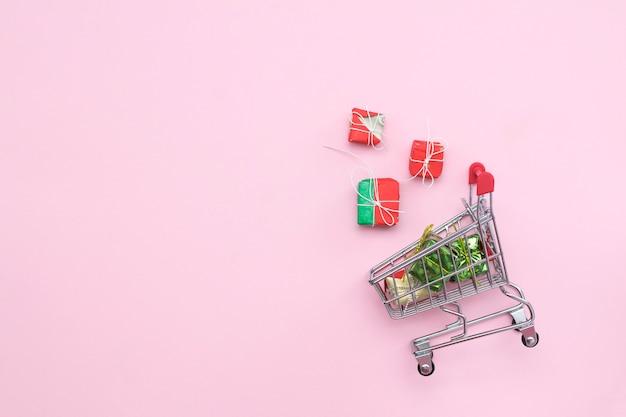 Wózek na zakupy na różowym tle z prezentami, widok z góry. copyspace. biznes, wyprzedaże, świąteczne zakupy.