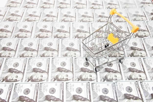 Wózek na zakupy na tle dolarów