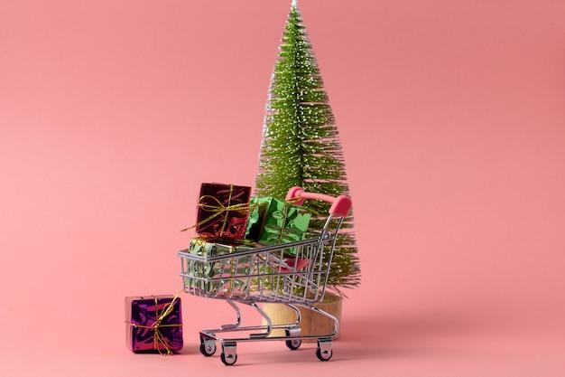 Wózek na zakupy pełen obecnych pudełek na choinkę na różowo