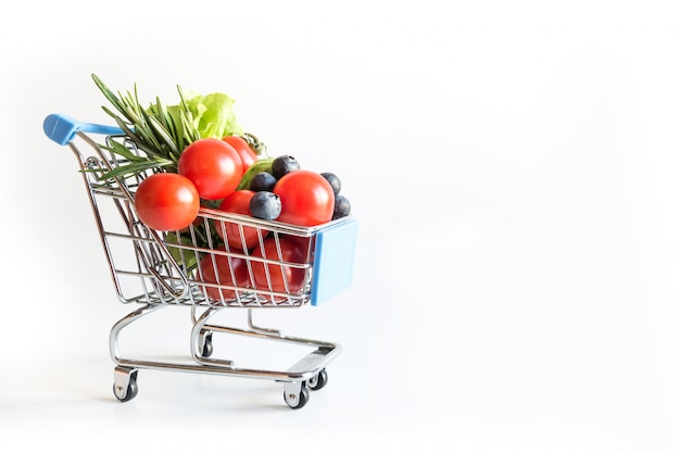 Wózek na zakupy pełen świeżych warzyw spożywczych na białym tle