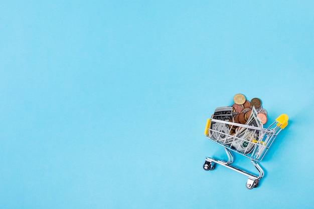 Wózek na zakupy wypełniający z monetami na kopii przestrzeni tle
