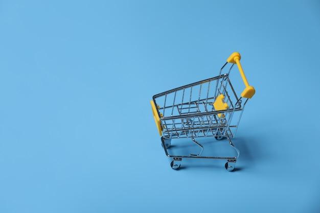 Wózek na zakupy z błękit ścianą z kopii przestrzenią. selektywna ostrość