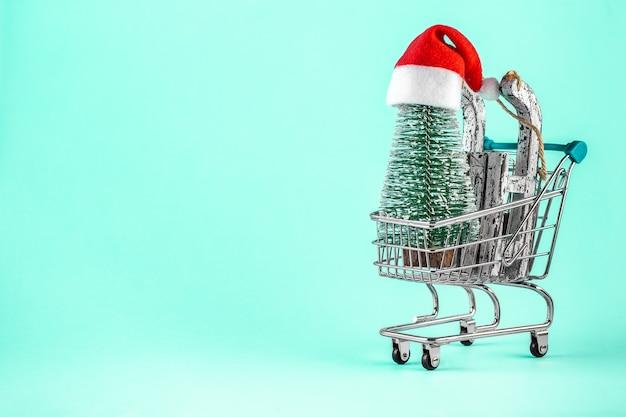 Wózek na zakupy z choinką i kapeluszem świętego mikołaja na niebieskim tle. wesołych świąt i szczęśliwego nowego roku kartkę z życzeniami. koncepcja ferii zimowych. skopiuj miejsce na tekst