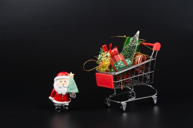 Wózek na zakupy z choinką i miniaturowymi pudełkami na prezenty oraz śnięty mikołaj