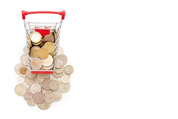 Wózek na zakupy z euro monetami jedzie w górę stosu starych i ośniedziałych rosyjskich monet na białym tle. wolne miejsce na tekst.