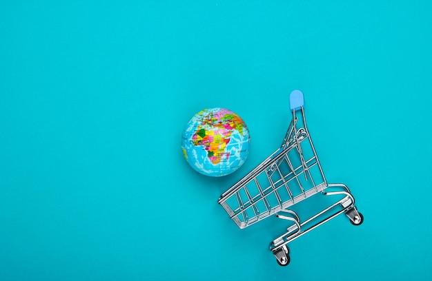 Wózek na zakupy z kulą ziemską na niebieskiej powierzchni