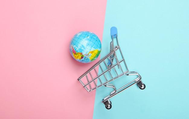 Wózek na zakupy z kulą ziemską na różowo-niebieskiej powierzchni