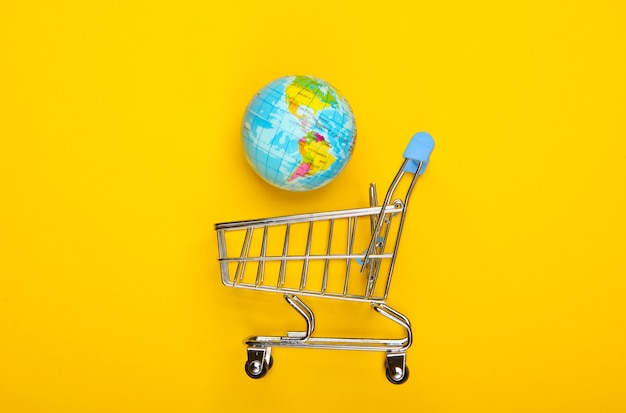Wózek na zakupy z kulą ziemską na żółtej powierzchni