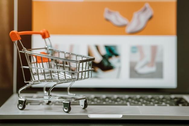 Wózek na zakupy z laptopem na stole. koncepcja zakupów online lub e-commerce w internecie w celu ochrony przed koronawirusem covid-19