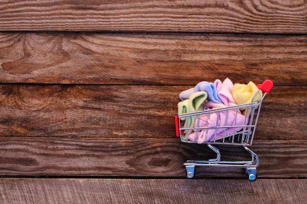 Wózek na zakupy z odzieżą na starym drewnianym tle. stonowany obraz.
